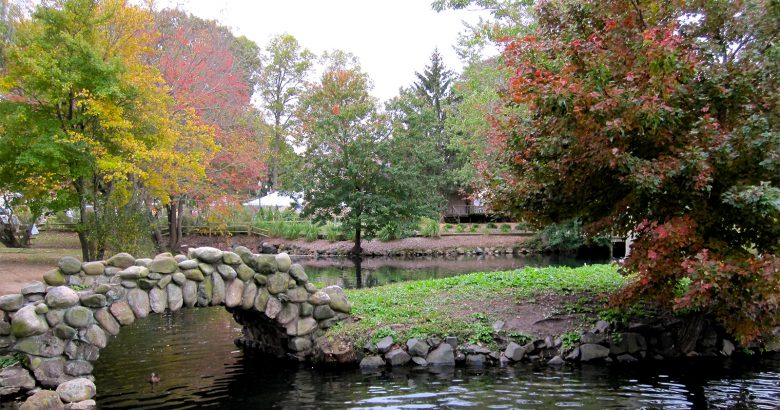Arched stone bridge over a pond leading to green grass, set in front of colorful trees in Autumn